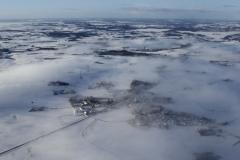vinter_luftfoto_-_landsby_under_slret_skydkke
